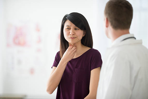 Telling a Doctor About Her Sore Throat stock photo