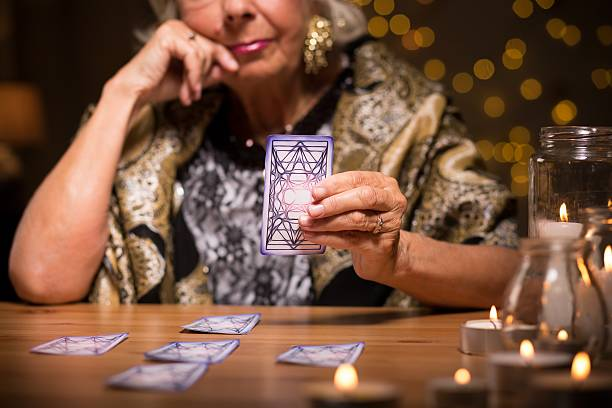Telling fortune from tarot cards Female seer telling fortune from tarot cards romani people stock pictures, royalty-free photos & images