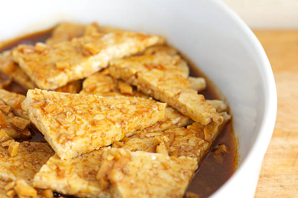 Tempeh Marinating with Garlic and Ginger in White Dish stock photo