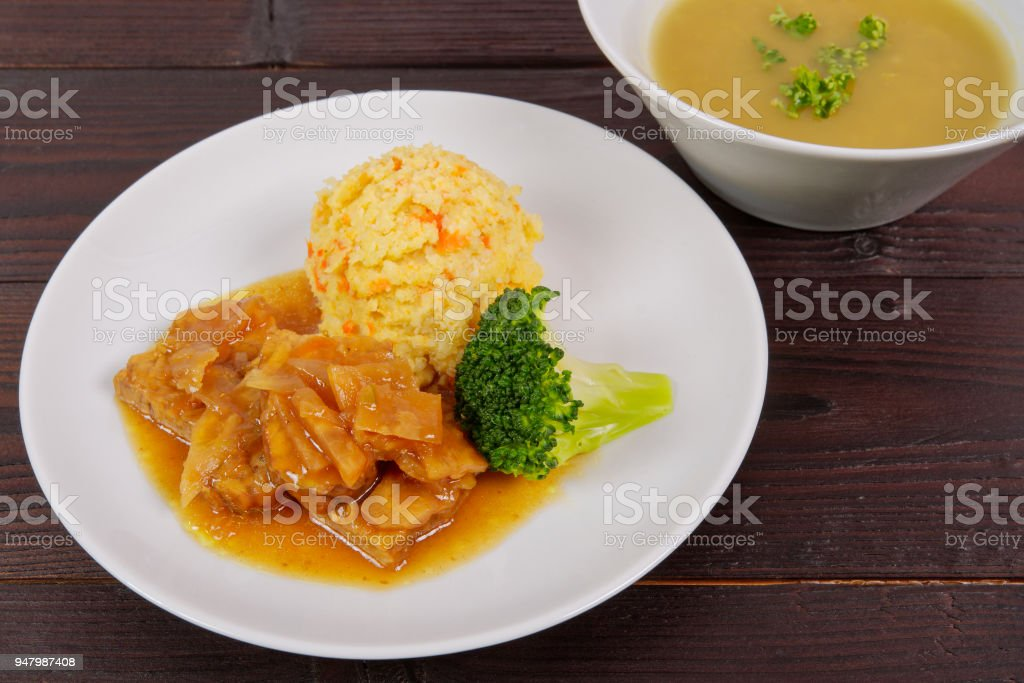 Tempeh on leek with pear purée on a table stock photo