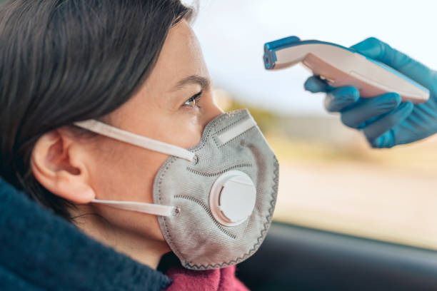 temperature check point - the woman behind the wheel of the car in an anti-virus mask is subjected to temperature measurement. - adenovirus foto e immagini stock