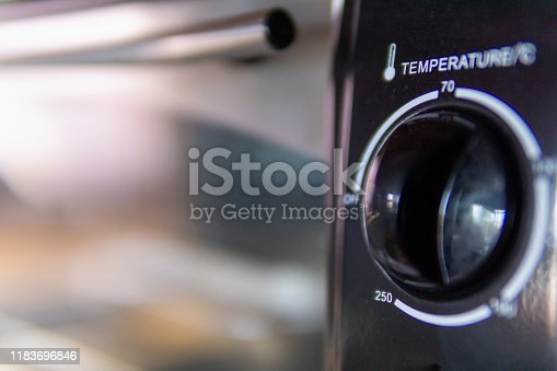 A close-up image of an oven door with temperature control dial.  The door is clean Aluminum with some flare and reflection.  The dial is circular and contains the word 'temperature' and has numbered settings thereon.  Copy space available, ideal background image.