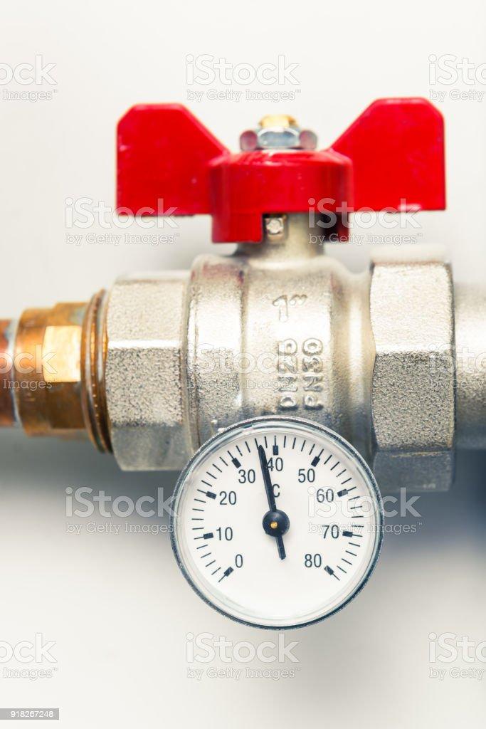 temperature gauge indicator with water tap in boiler-room stock photo