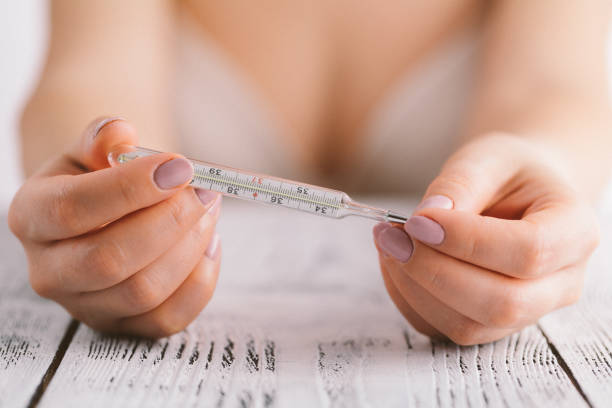 Temperature measurement in a natural family planning method. stock photo