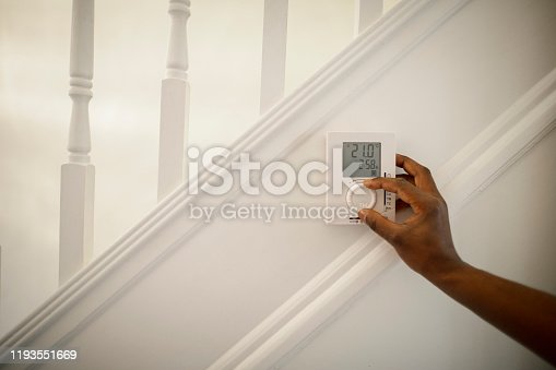 Shot of an unrecognisable man turning down a thermostat in his home.