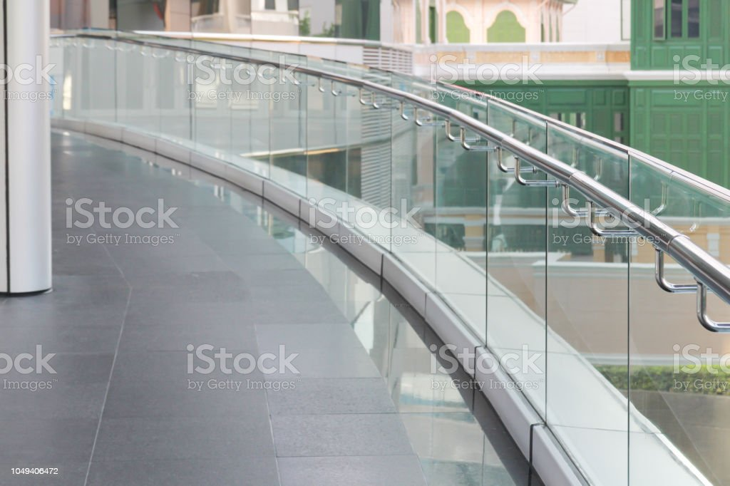 tempered glass of walk way balcony with stainless steel handrail.