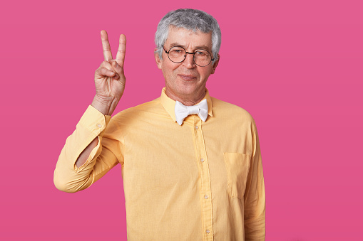 Tempered old senior points two fingers up, wears yellow clothes and white bow tie. Calm smilling pensioner with rounded black spectacles poses against rose wall in studio. People concept.