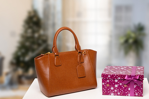 Template for christmas sale. Elegant brown female luxury handbag and a gift box on table against blurred xmas tree background indoor. Advertising fashionable woman accessories.