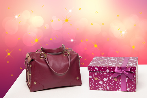 Template for christmas sale. Luxury and stylish womens leather handbag and a gift box on table against abstract festive background . Advertising fashionable woman accessories.
