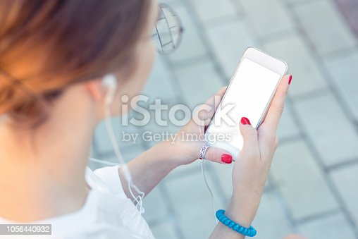 istock Template of a close up on a woman's hands, holding a phone while wearing headphones. Communicate inside the copy space about phone applications, music listening, street style, youth 1056440932