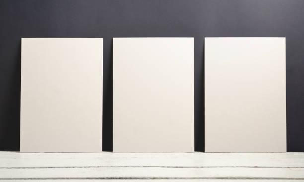 modelo de um mocup de três cartazes sobre um fundo preto e uma mesa de madeira. - três objetos - fotografias e filmes do acervo