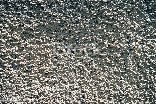 973649382istockphoto Template of foundation of old building from crushed stone close-up. Pattern of chippings. White detailed background from texture of gravel with copy space. 1034620604