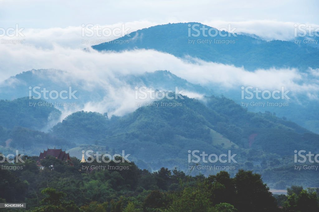A Temple and pagoda on top of Beautiful mountains with clouds and fogs. stock photo