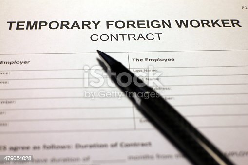 Someone filling out Temporary Foreign Worker Contract.