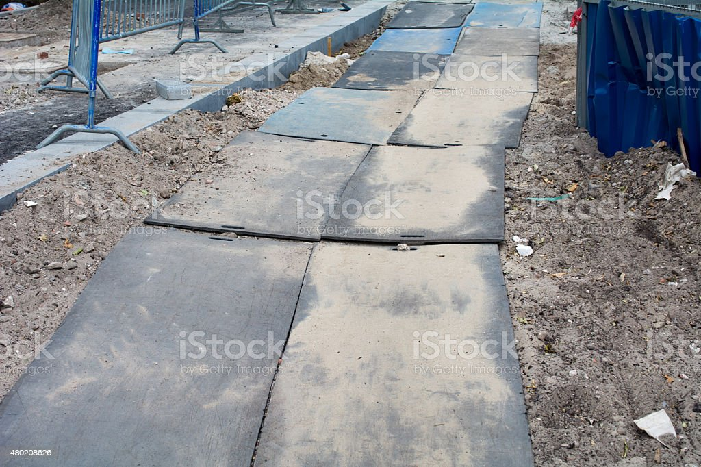 Temporary sidewalk with large plates stock photo