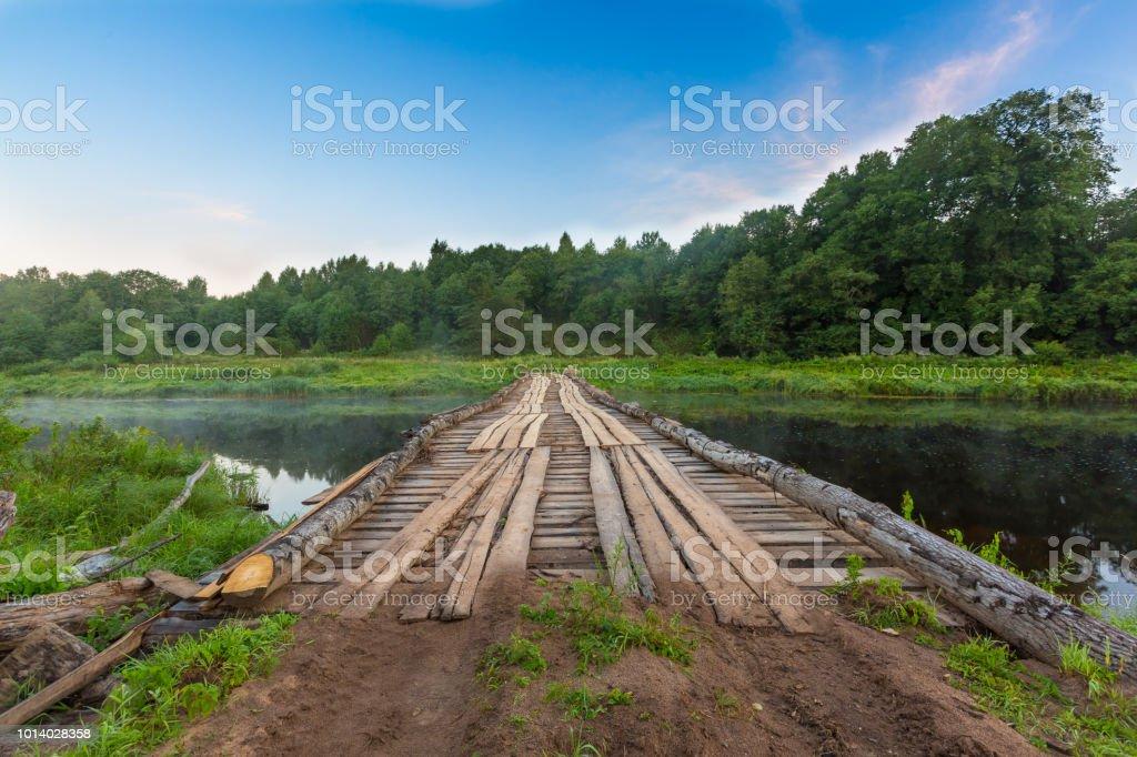 Hölzerne Behelfsbrücke über Fluss für schwere Lastkraftwagen, Lastwagen, Autos und Fahrzeuge zur Beförderung Holz während der Entwaldung – Foto