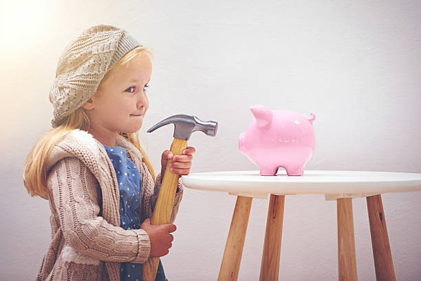 Tempting, isn't it? A little girl standing next to her piggy bank with a hammerhttp://195.154.178.81/DATA/i_collage/pi/shoots/783492.jpg allowance stock pictures, royalty-free photos & images