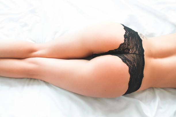 tempting lady perfect body black lace lingerie Cropped shot of tempting lady with perfect slim body in black lace lingerie lying down on bed in provocative pose. hot sexy butts stock pictures, royalty-free photos & images