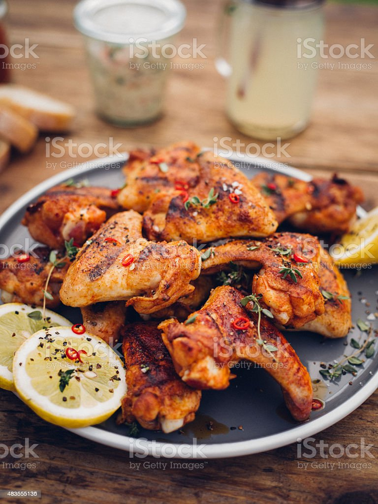 Tempting spicy chicken wings on a plate with lemon slices stock photo