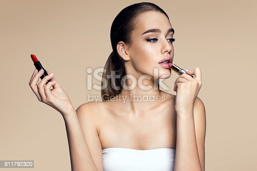 istock Tempting young woman with lipstick 511792320