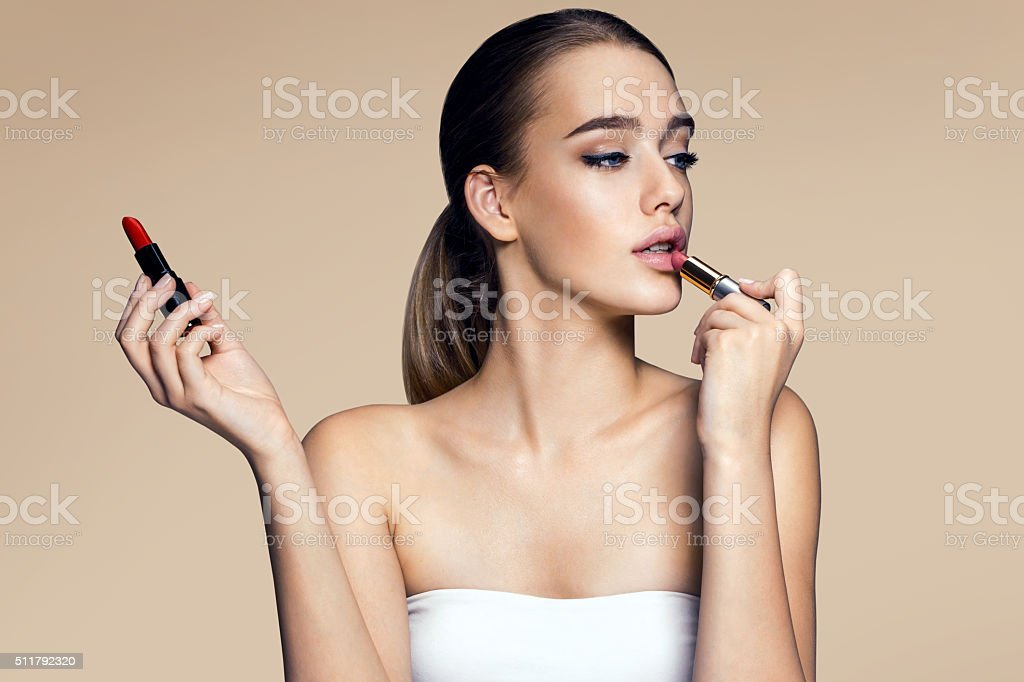 Tempting young woman with lipstick stock photo