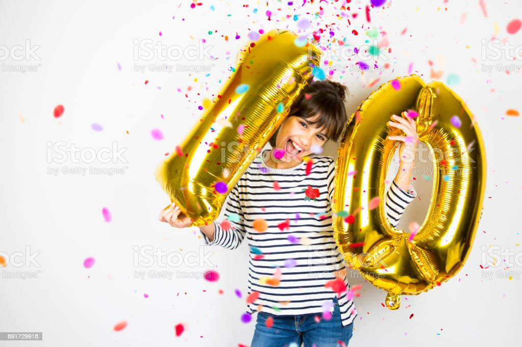 Ten birthday party girl with golden balloons and confetti royalty-free stock photo