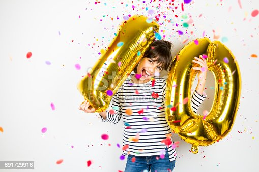istock Ten birthday party girl with golden balloons and confetti 891729916
