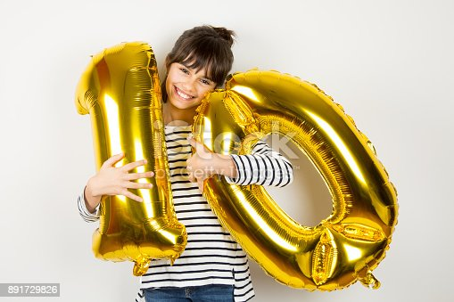 istock Ten birthday party girl with golden balloons 891729826