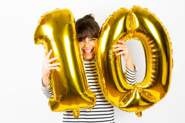 Ten birthday party girl with golden balloons stock photo