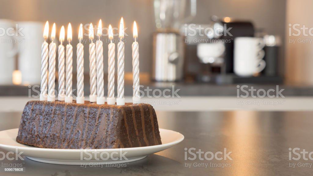 Ten Burning Candles On A Birthday Cake In Modern Kitchen Stock