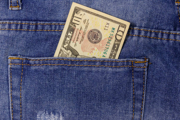 Ten dollars banknote in the pocket of blue jeans stock photo