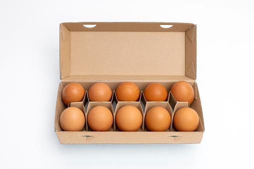 Ten eggs in brown carton on white