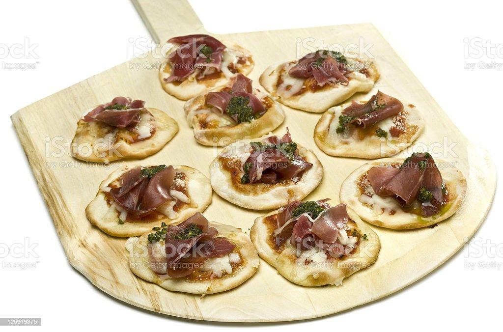 Ten mini meat pizzas on wooden spatula royalty-free stock photo