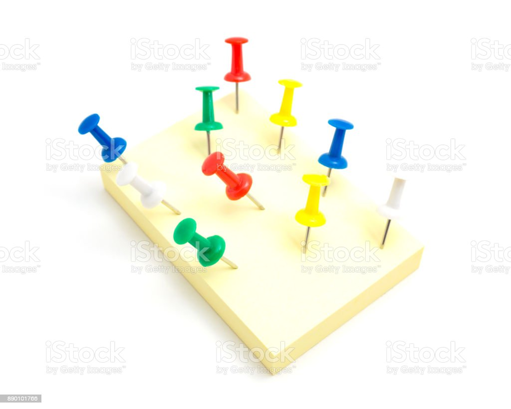 Ten push pins and yellow sticky note on isolated white background stock photo