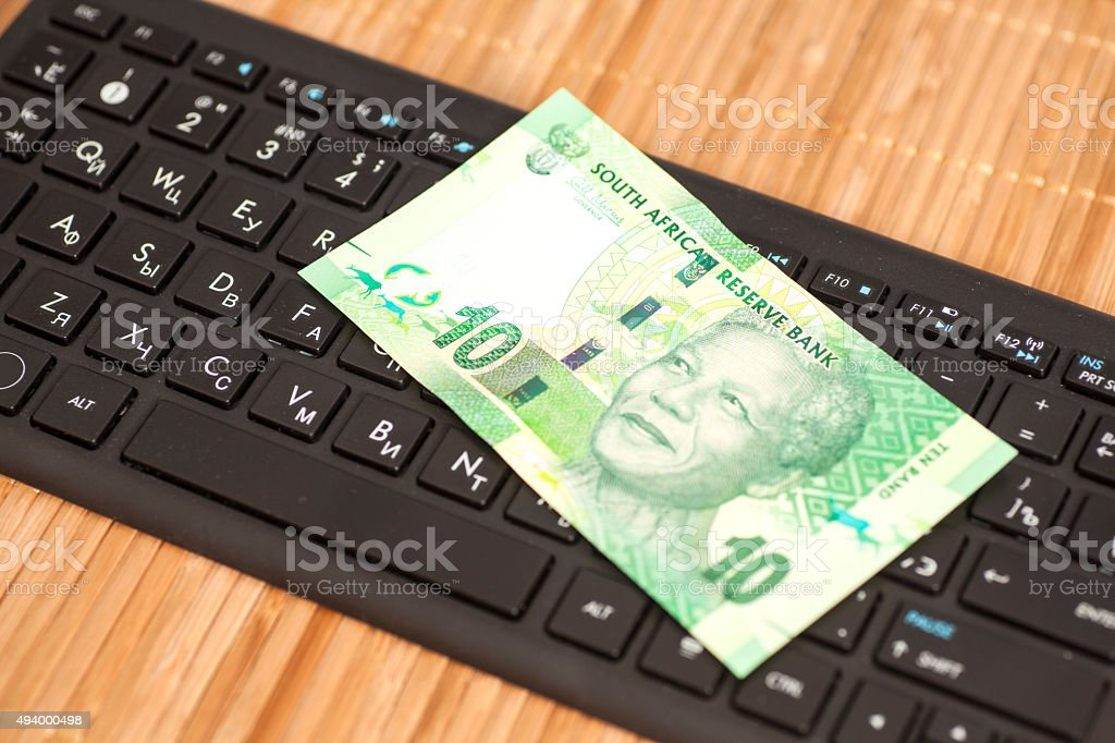 Ten South African Rand on computer keyboard stock photo
