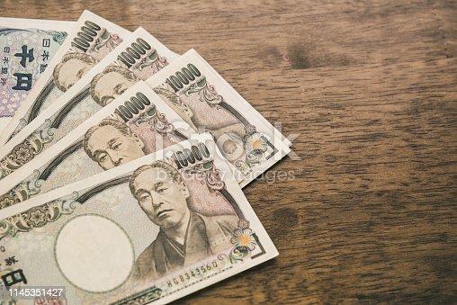 istock Ten thousand Japanese Yen banknotes on wood table 1145351427