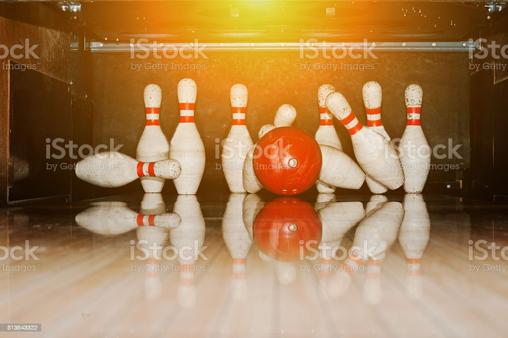 Ten white pins in a bowling alley with ball hit stock photo
