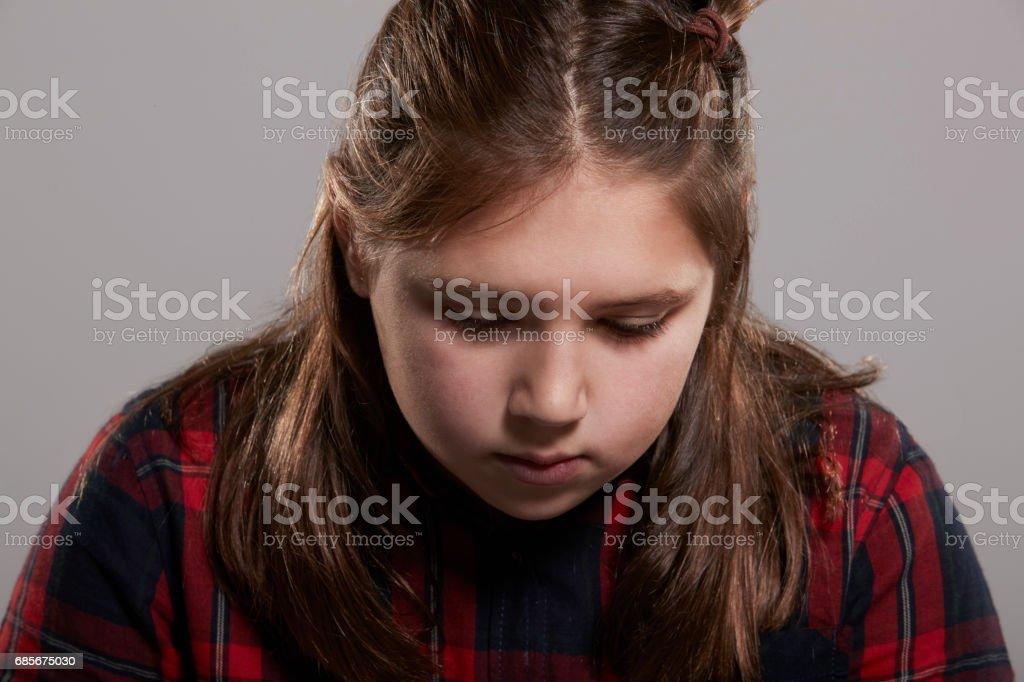 Menina de dez anos olhando para baixo, cabeça e ombros - foto de acervo