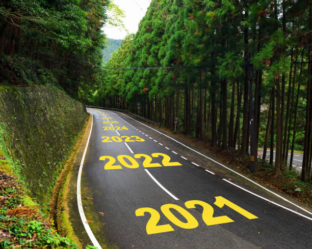 Ten years from 2021 to 2030 on highway road and white marking lines in the forest Happy new year and road to success concept the way forward stock pictures, royalty-free photos & images