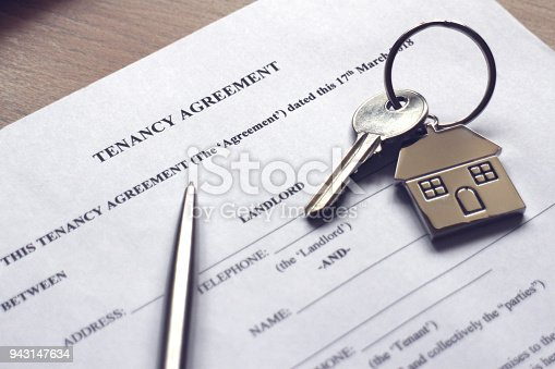 A house key resting on a tenancy agreement contract.