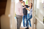 a young couple view a property guided by an estate agent. They are standing in the hallway of house and receiving the keys to the property