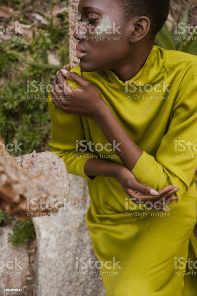 anbud afroamerikanska kvinna med slutna ögon och glitter makeup poserar i gul klänning - Royaltyfri Afrikanskt ursprung Bildbanksbilder
