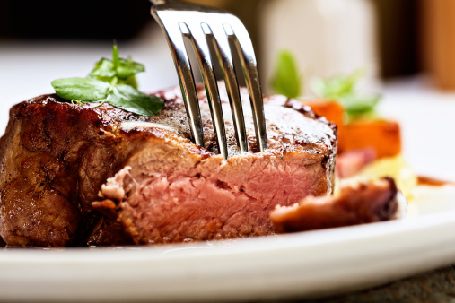 A fork pierces a juicy, succulent grilled fillet steak, grilled medium rare.