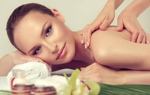 zarte und weiche hände des massage-spezialisten macht massage auf dem rücken der jungen frau. - saunazubehör stock-fotos und bilder