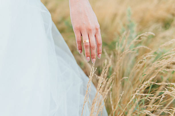 tender beautiful bride's hands on elegant white wedding dress closeup - beyaz elbise stok fotoğraflar ve resimler