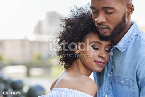Tender black couple hugging with closed eyes outdoors