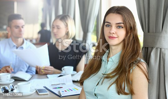Portrait of gorgeous girl sitting near group of company workers. Corporate female looking away with joy and anticipation. People discussing important graphs and charts. Restaurant interior