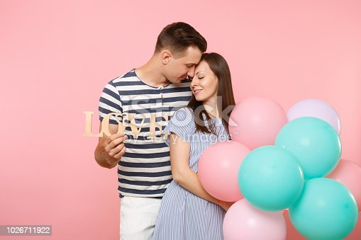 istock Tender couple hold wooden word letters love. Woman and man in blue clothes celebrating birthday holiday party on pastel pink background with colorful air balloons. People sincere emotions concept. 1026711922