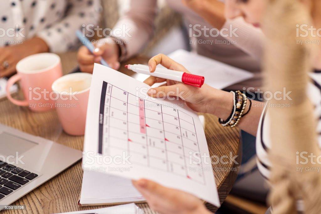 Zarte weibliche Hände halten Kalender – Foto
