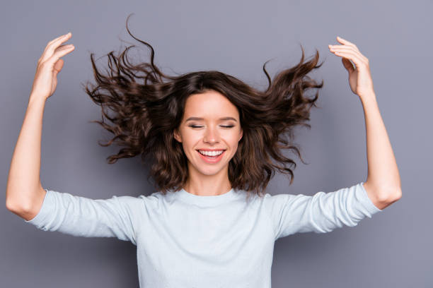 Tender gently sweet lady in style stylish casual clothes with he Tender gently sweet lady in style stylish casual clothes with her modern curly wave hairdo close eyes raised hands up feel free enjoy moment she isolated on gray background hair stock pictures, royalty-free photos & images